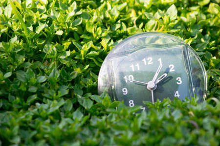 the transition to summer time, the arrival of spring, the clock on the background of bright green spring grass with a place for the inscription, a bright sunny day Stock Photo - 125217356
