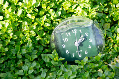 the transition to summer time, the arrival of spring, the clock on the background of bright green spring grass with a place for the inscription, a bright sunny day Stock Photo - 125217498