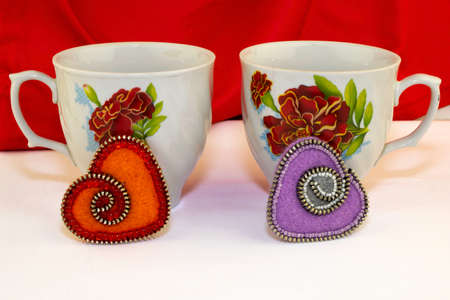 Valentine's day, handmade products from felt , two tea mugs and hearts of felt are on the table, the red background