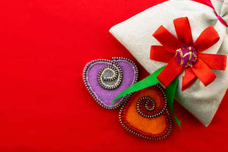 Valentine's day, handmade products from felt , two hearts made of felt and a gift bag on a red background Stock Photo