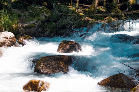 the water of a stormy mountain river flowing among stones and boulders Фото со стока