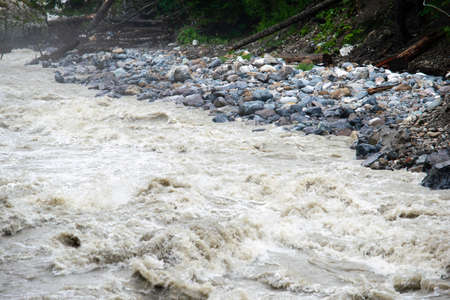the water of a stormy mountain river flowing among stones and boulders Stok Fotoğraf