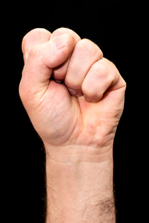 male hand clenched into a fist on a black background Stock fotó