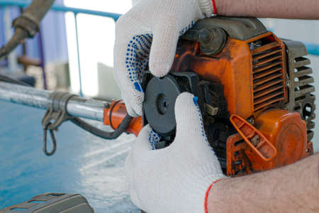 the master in working gloves repairs the engine of the old gas trimmer removes the cover of the air filter