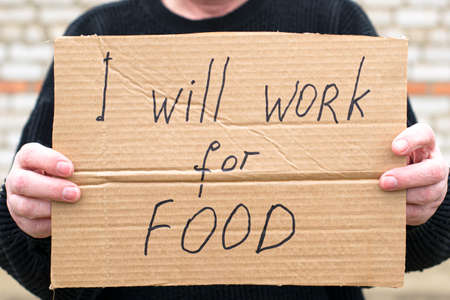 unemployed person holding a cardboard sign with a inscription i will work for food