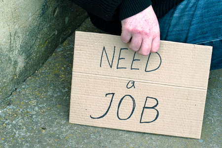 unemployed man sitting on the ground holding the cardboard sign saying need a job