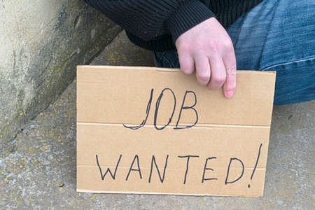 unemployed man sitting on the ground holding a cardboard sign saying job wanted