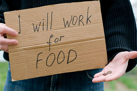the unemployed person holds in his hand a cardboard tablet with the inscription i will work for food in his other hand the remaining coins