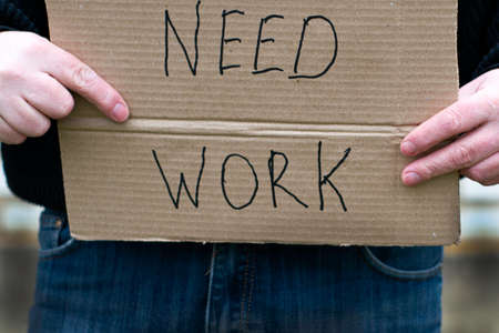 unemployed person holding a cardboard sign with a inscription need work