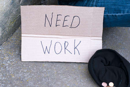 unemployed man sitting on the ground holding the cardboard sign saying need work next to is a hat with alms coins