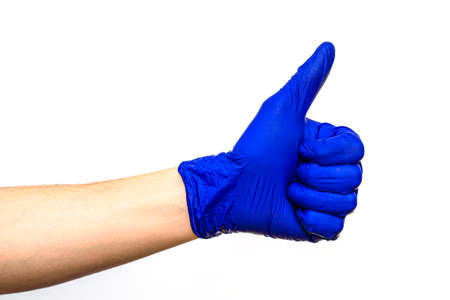 hand in blue rubber protective medical surgical glove on a white background hand clenched fist thumb raised up
