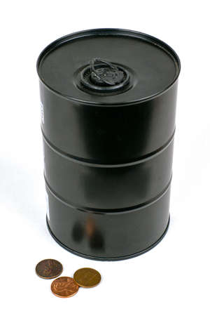 The concept of falling oil prices: a standing black iron barrel, small coins are scattered next to it on a white background