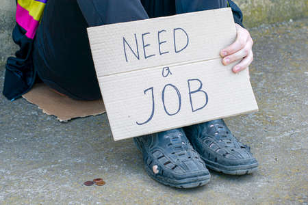 unemployed in old shoes holds in his hand a cardboard tablet with the inscription need a job on the ground are small coins of alms