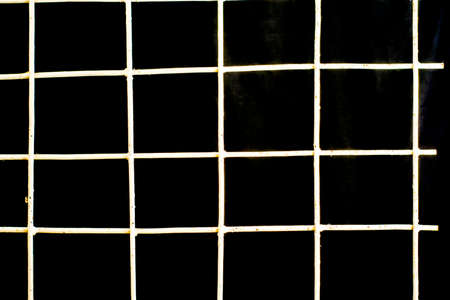 white iron grate on a black background