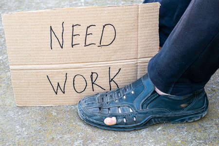unemployment concept man in old torn shoes sits on the ground at his feet cardboard sign saying need work Standard-Bild