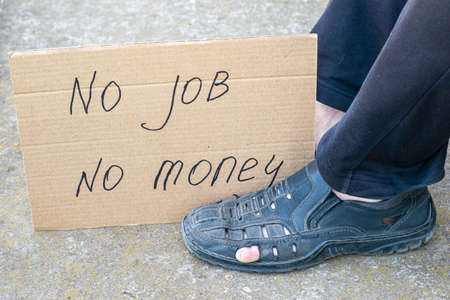 unemployment concept man in old torn shoes sits on the ground at his feet cardboard sign saying no job no money