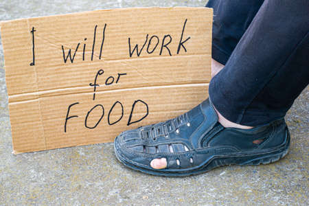 unemployment concept man in old torn shoes sits on the ground at his feet cardboard sign saying i will work for food Foto de archivo