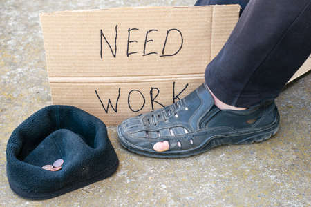 unemployment concept man in old torn shoes sits on the ground at his feet cardboard sign saying need work next to a cap with small alms coins.
