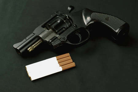 concept smoking - suicide pistol lying on a dark background next to cigarettes tkmny key Stock Photo