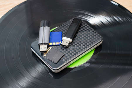 modern storage media hard drive and flash cards lie on an old gramophone record