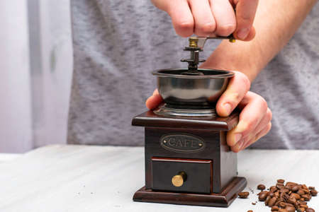 man grinds coffee beans in a manual coffee grinder
