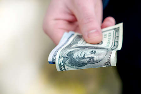 the hand holds out several hundred dollar bills folded in half. High quality photo