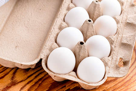 white chicken eggs in a paper tray stand on the table close up. High quality photo