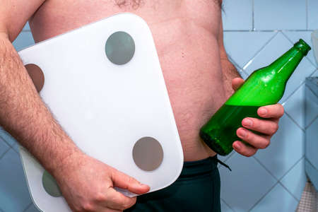 a fat man holds a bottle of beer and a scale concept diet proper nutrition. High quality photo