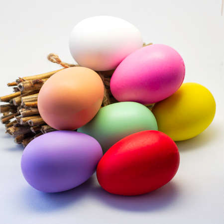 colorful Easter eggs and a bundle of firewood on a light background happy Easter concept. High quality photo