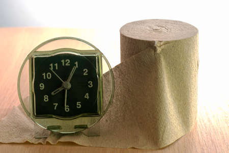 a roll of toilet paper and a clock on the shelf concept daily routine proper nutrition. High quality photo