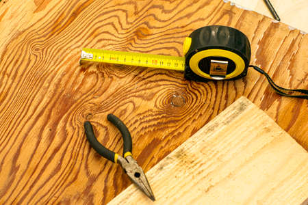 measuring tape measure board and pliers on the workbench. High quality photo