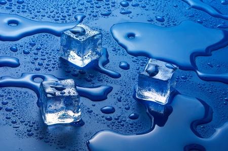 cubetti di ghiaccio: cubetti di ghiaccio di fusione su sfondo blu Archivio Fotografico