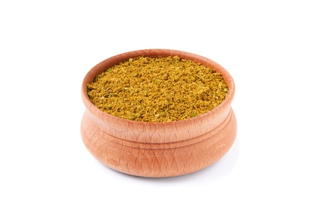 karri: mixture of dry spices in a wooden salt-cellar on a white background Stock Photo