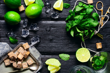 Ingredients for the preparation of cold and refreshing mojito lime, mint, sugar Thatched ice. In the old charred wooden background. Stock Photo