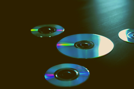 Compact discs on the background artistic future CD DVD colorful media film music sound technology time generation vintage minimal background wallpaper texture closeup 80s 90s 2000th years Foto de archivo