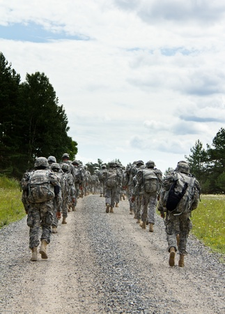 Soldiers are marching on a gravel road photo