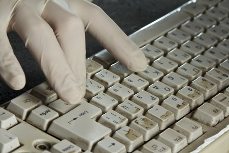 Old dirty computer keyboard used with gloves photo