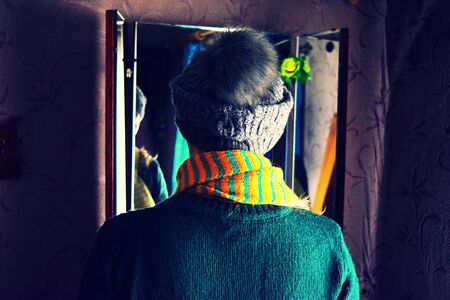 the girl looks at herself in the mirror, winter hat, jacket and striped scarf