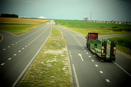 Heavy truck moving on a highway on a sunny summer day