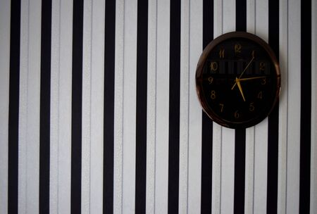 striped black and white wallpaper on the wall with a clock Фото со стока