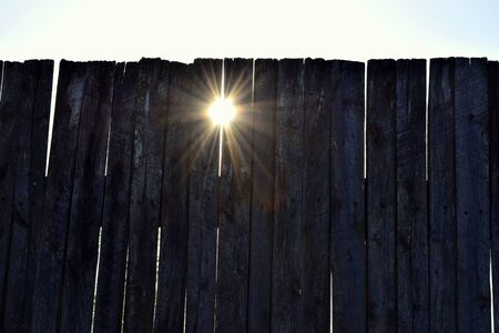 rays of the sun shine through the cracks of a wooden fence