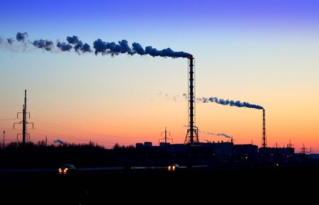 smoke from the chimneys of a chemical plant against the backdrop of a sunset blue and pink sky Archivio Fotografico