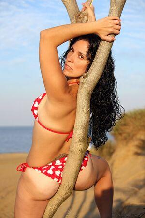 babe: Pretty Girl In String Bikini Leans On Tree