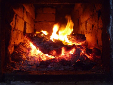 Firewood blaze in stove from brick photo
