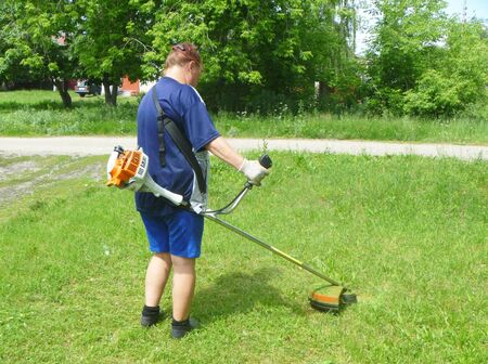 Woman mowns herb by lawn mower photo