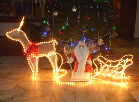 blazes: Luminous deer with sled and Grandparent by Frost under fir tree with toy on dark background