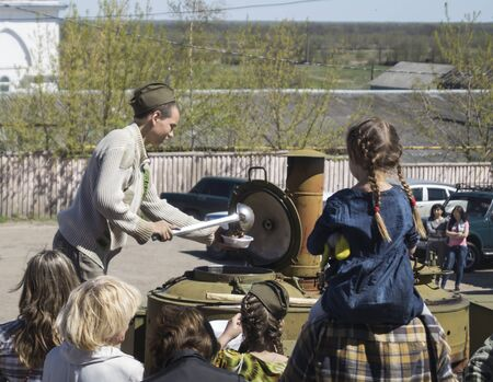 oversea: Teenager in oversea cap superimposes porridge from field kitchen at festive day of the Victory in city Mstyora,Russia