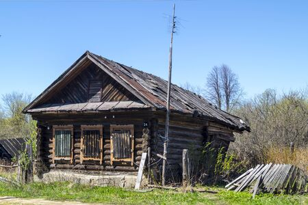 thrash: Rubble of the old wooden building on background blue sky in Russia