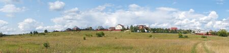 eminence: Year panorama of the cottages on background blue sky in Russia