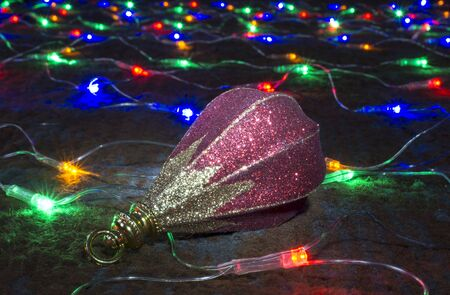 blazes: Toy rests upon festoon of the colour lights on dark background